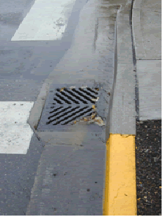 A storm drain next to a curb